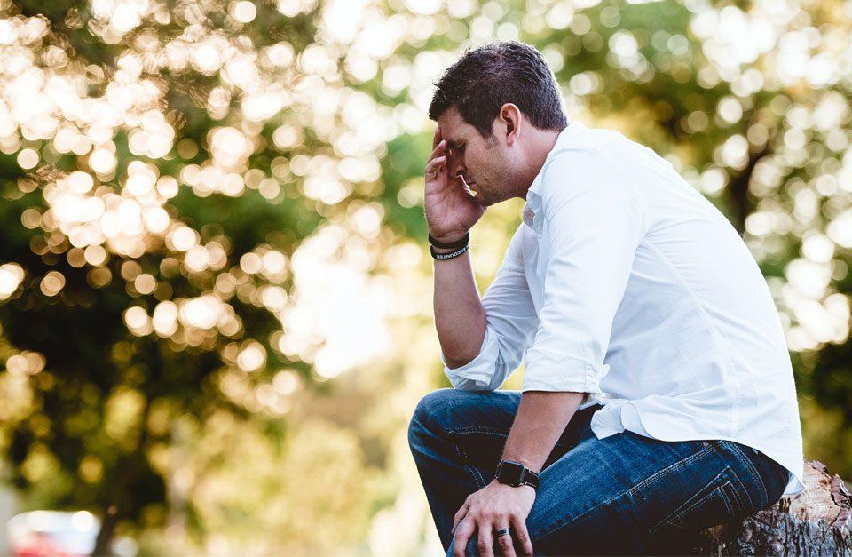 Depressiver Mann in der Natur - Stressdepression - DER ZUSAMMENHANG ZWISCHEN STRESS UND DEPRESSIONEN